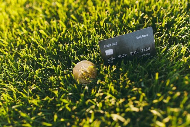 Close-up credit bank zwarte kaart, bitcoin, munt van gouden kleur op levendige lente groen gras, zonneschijn gazon. natuur textuur, groene achtergrond voor behang. financiënontwerp, virtueel muntconcept.