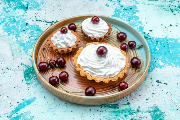 Close-up cupcake met slagroom en wat kersen op blauw,
