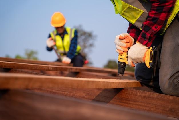 Close-up dakdekker die werkt aan de dakconstructie van een gebouw op de bouwplaats, dakdekker met behulp van lucht of pneumatisch schiethamer en installeren op houten dakconstructie.