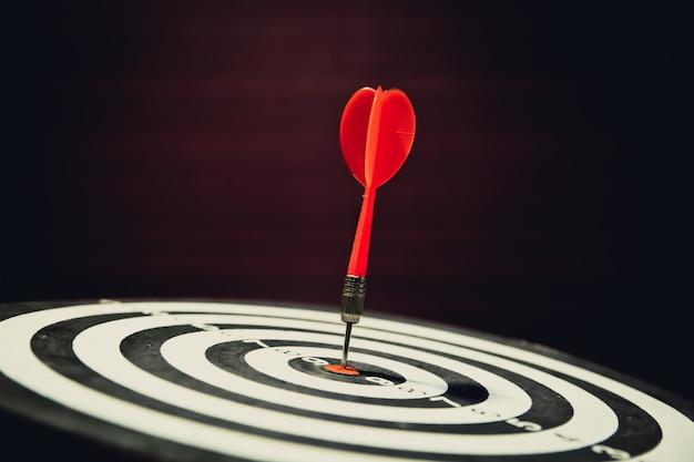 Close-up dartbord met pijl die in het doelcentrum raakt.