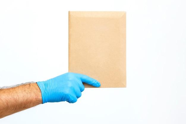 Close-up de hand van een mannelijke koerier in een medische handschoen houdt een envelop op een witte achtergrond. hand van postbode die post in medische handschoen levert.