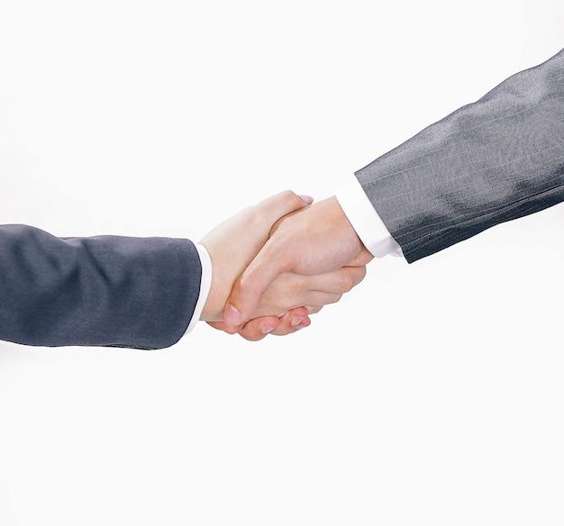Close-up. de zakenpartners van de handdruk. geïsoleerd op een witte muur. het concept van partnerschap