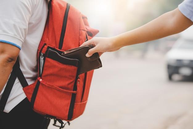 Close-up de zakkenroller pikt geld op van toeristen die op reis zijn.