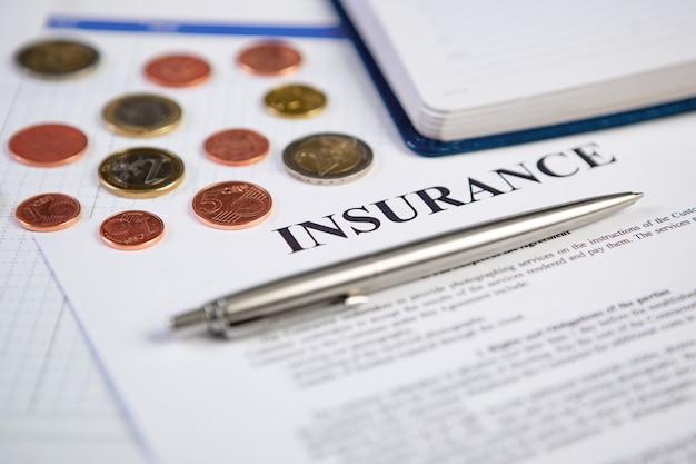 Close-up de zilveren moderne pen op verzekeringscontract met muntstukken en planning in muur.