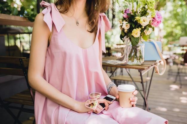 Close-up details van handen van vrouw zitten in café in zomer mode-outfit, roze katoenen jurk, zonnebril, koffie drinken, stijlvolle accessoires, ontspannende, trendy kleding