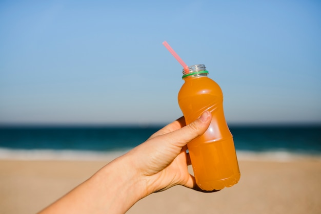 Close-up die van de hand van de vrouw een jus d'orange plastic fles met het drinken van stro houden bij strand