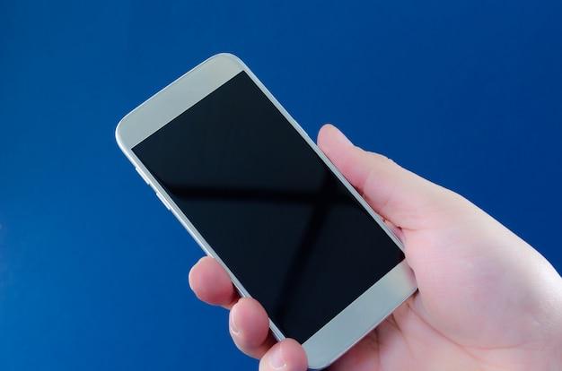 Close-up die van de hand van de zakenman mobiele telefoon met het zwarte lege scherm houdt. over blauwe ruimte.