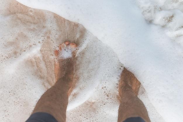 Close-up die van de voeten van het mannetje in oceaanwater is ontsproten