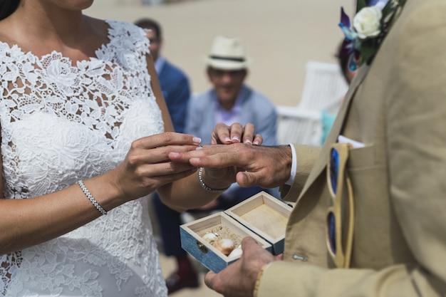 Close-up die van een bruid is ontsproten die een trouwring op de hand van de bruidegom zet