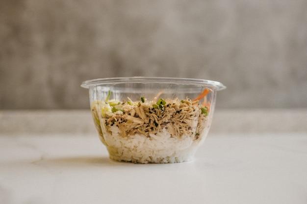 Close-up die van een duidelijke plastic kom met binnen voedsel is ontsproten