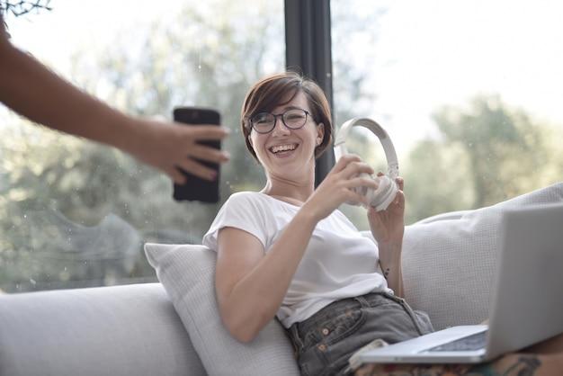 Close-up die van een glimlachende vrouw is ontsproten die een telefoon in iemands handen bekijkt