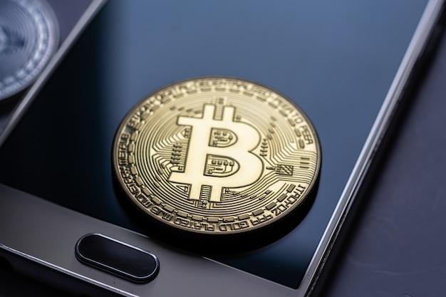 Close-up die van een groot muntstuk is ontsproten dat bovenop een mobiele telefoon wordt geplaatst