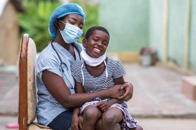 Close-up die van een jongen en een arts is ontsproten die sanitaire maskers dragen