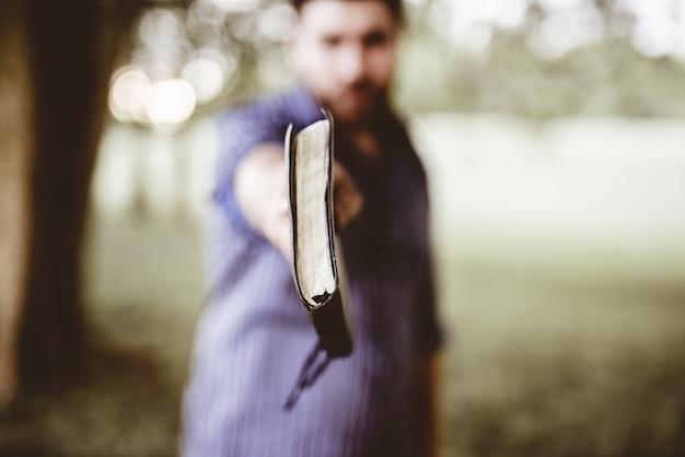 Close-up die van een mannetje is ontsproten dat de bijbel naar de camera houdt