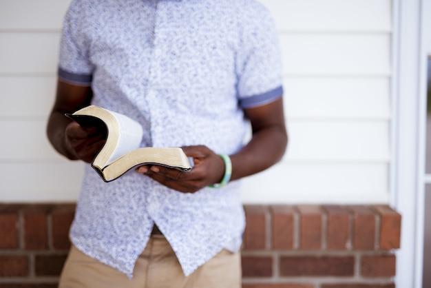 Close-up die van een mannetje is ontsproten dat de bijbel opent