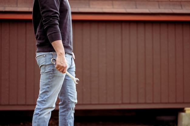 Close-up die van een mannetje is ontsproten dat een hulpmiddel in zijn hand houdt