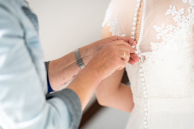 Close-up die van een mannetje is ontsproten dat haar vrouw helpt die een bruidsjurk draagt