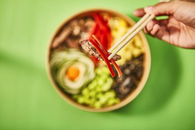 Close-up die van een menselijke hand is ontsproten die een stuk vlees met spaanse peper door chinese stokken houdt