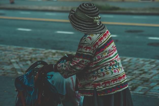 Close-up die van een oud wijfje is ontsproten dat een hoed draagt die een wandelwagenvervoer houdt