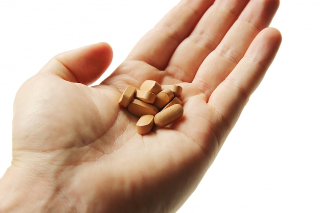 Close-up die van een persoon is ontsproten die een bos van pillen op wit houdt