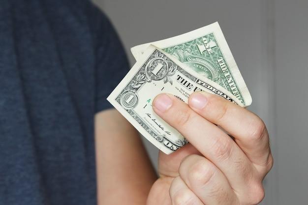 Close-up die van een persoon is ontsproten die een dollarbiljet van de vs op zijn hand houdt