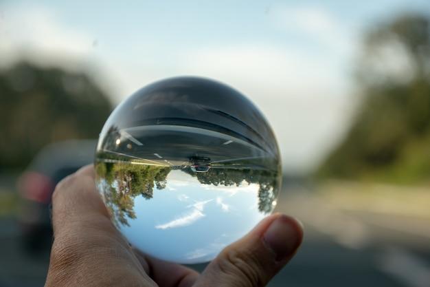 Close-up die van een persoon is ontsproten die een kristallen bol met de weerspiegeling van bomen houdt