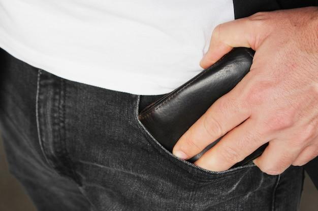 Close-up die van een persoon is ontsproten die een leerportefeuille in zijn zak zet