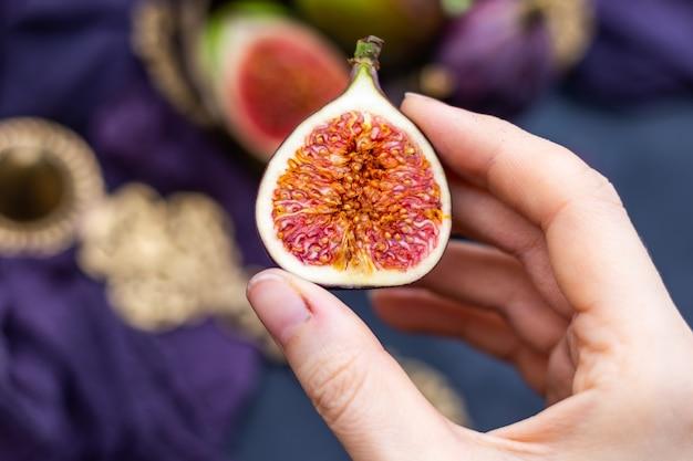 Close-up die van een persoon is ontsproten die een verse fig. houdt