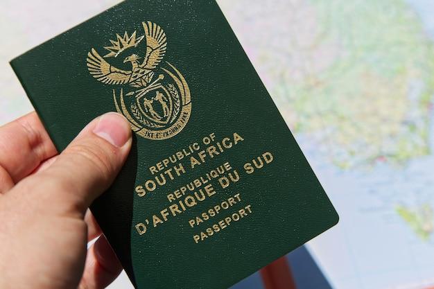 Close-up die van een persoon is ontsproten die het paspoort van de republiek zuid-afrika houdt