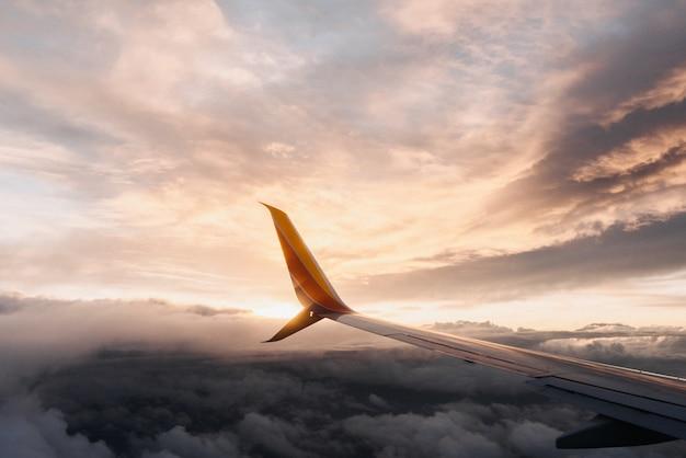 Close-up die van een vliegtuigvleugel is ontsproten in een rozeachtige hemel