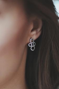 Close-up die van een vrouw is ontsproten die een mooie hangeroorbel draagt
