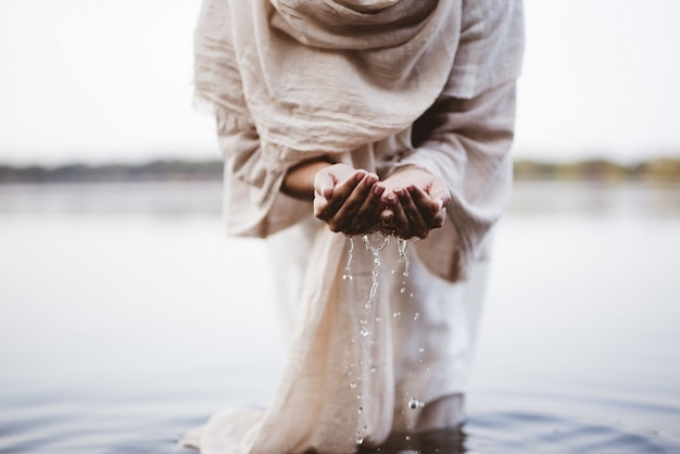 Close-up die van een wijfje is ontsproten dat een bijbels gewaadwater met haar palmen draagt