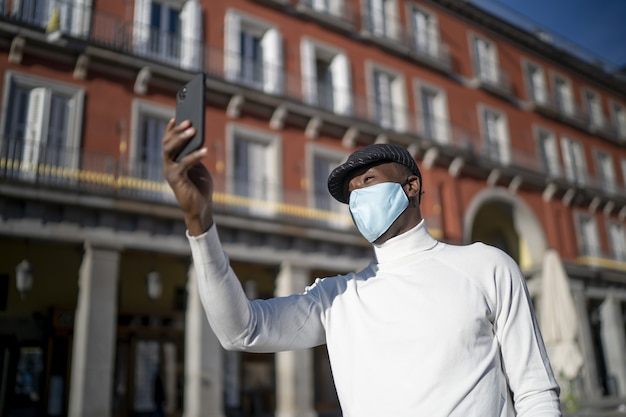Close-up die van een zwarte mens is ontsproten die zijn telefoon vasthoudt die een coltrui-concept van het nieuwe normaal draagt
