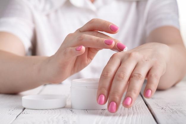 Close-up die van handen is ontsproten die vochtinbrengende crème toepassen. de vrouw die van de schoonheid een glaskruik huidroom houdt