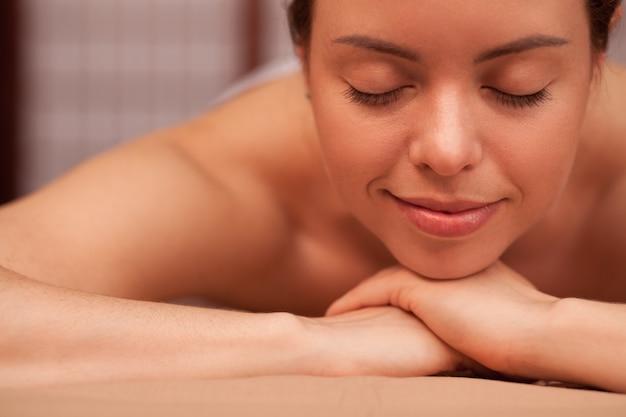 Close-up die van het gelukkige mooie gezonde vrouw glimlachen, op kuuroordcentrum ontspant. jonge aantrekkelijke vrouw die met onberispelijke vlotte huid van kuuroordbehandeling geniet. recreatie, verjonging en verwennerij