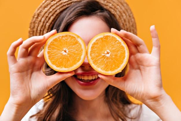 Close-up die van jong meisje in schipper is ontsproten die haar ogen behandelt met sappige sinaasappelen.