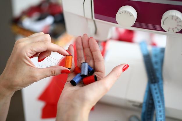 Close-up die van naaister bos van verschillende kleurrijke spoelen van draden in de hand houden
