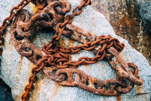 Close-up die van oude roestige kettingen is ontsproten die op de rots worden geplaatst
