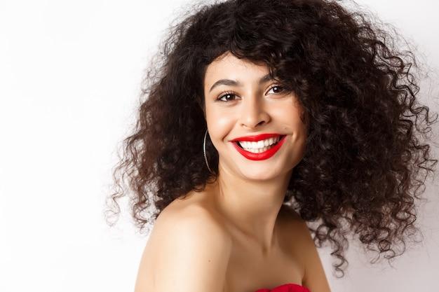 Close-up die van vrolijke glimlachende vrouw met rode lippenstift en krullend kapsel, gelukkig kijkt, zich over witte achtergrond bevindt.
