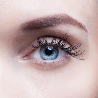 Close-up die van vrouwenoog is ontsproten met dagmake-up