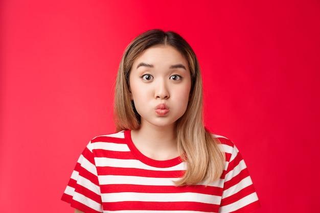 Close-up dom schattig aziatisch blond meisje pruilend maken speels gezicht vouwen lippen adem inhouden staan rode rug...