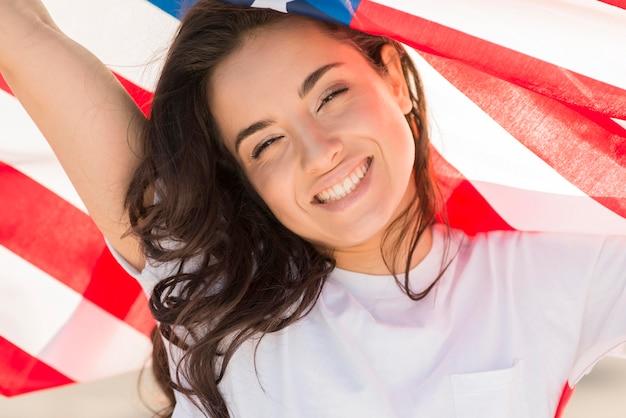 Close-up donkerbruine vrouw die de grote vlag van de vs en het glimlachen houdt