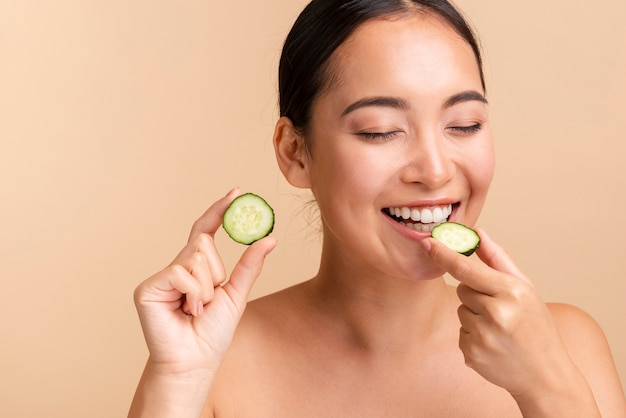 Close-up donkerbruine vrouw het bijten komkommerplak