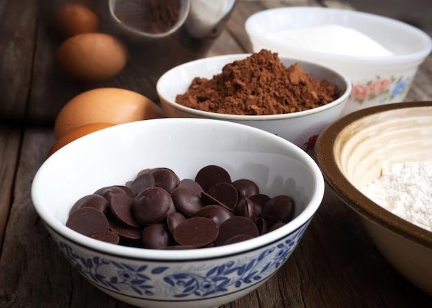 Close-up donkere chocolade in kleine kom. browniesingrediënten op houten lijst.
