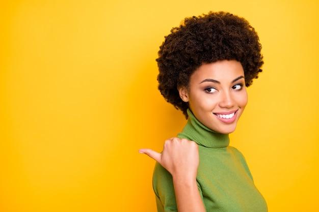 Close-up draaide portret van vrolijke positieve leuke trendy vrouw wijzend in de lege ruimte met haar duim lachend toothily.