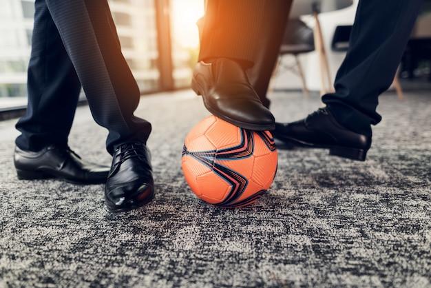 Close-up drie mannen in zwarte schoenen spelen een oranje bal
