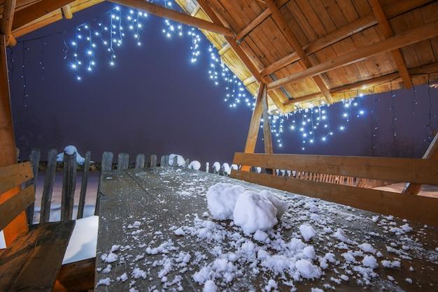 Close-up drie sneeuwballen liggen op een houten tafel onder het dak van een prieel met nieuwjaarslichten. pittoreske bergachtige plek met sparrenbos op ijzige winteravond tijdens de kerstvakantie