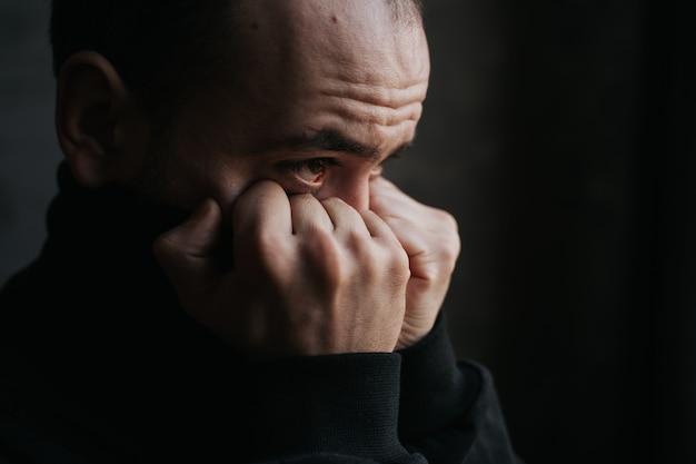 Close-up, droevige bebaarde man op zoek van raam. dagdroom, nadenken en denken concept. binnen