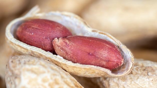 Close-up droge pinda's in shells op pinda'sachtergrond op houten lijst.