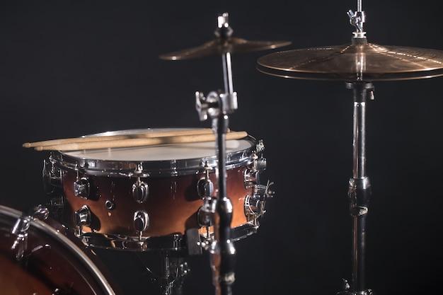 Close-up drumstel in een donkere kamer tegen de achtergrond van de schijnwerpers. koperen platen op een koude achtergrond